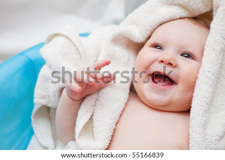 A beautiful smiling baby wrapped in quilt - stock photo