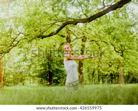 A beautiful smiling caucasian girl doing yoga and sport outdoors in a green summer forest.