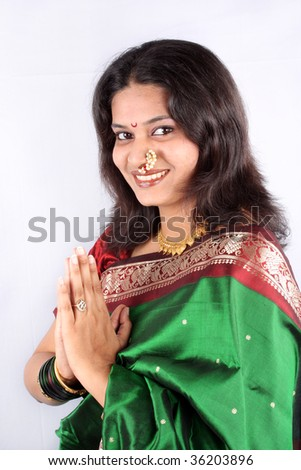 A beautiful smiling Indian woman in a traditional green saree with a welcome gesture of Namaste, used in India like Hello in western countries. - stock photo
