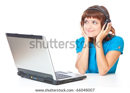 a beautiful smiling red-haired girl with a laptop is listening to the music. isolated on white background - stock photo