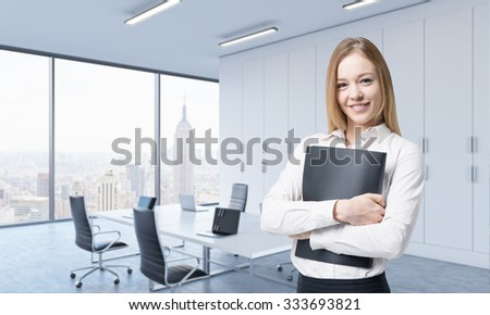A beautiful smiling woman holds a black document folder in the modern panoramic office. New York view. - stock photo