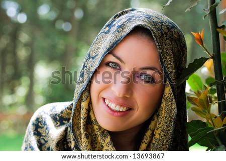 A beautiful smiling woman in garden wearing a traditional cape