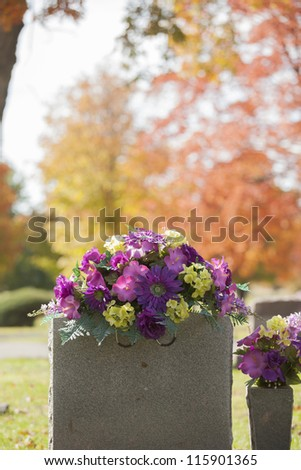 A beautiful spray of purple flowers grace the top of a tombstone in the fall. - stock photo