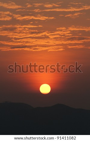 a beautiful sun rise with mountain foreground - stock photo