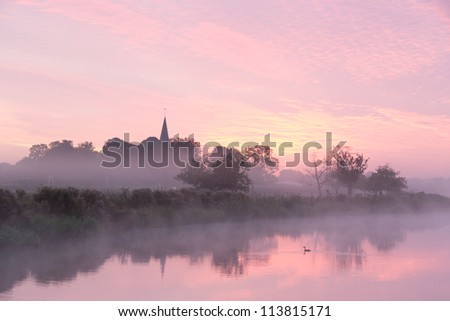 A beautiful sunrise in the Netherlands with autumn fog - stock photo