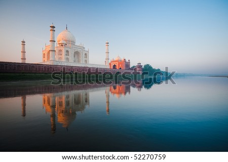 A beautiful sunrise lights the side of the Taj Mahal. - stock photo
