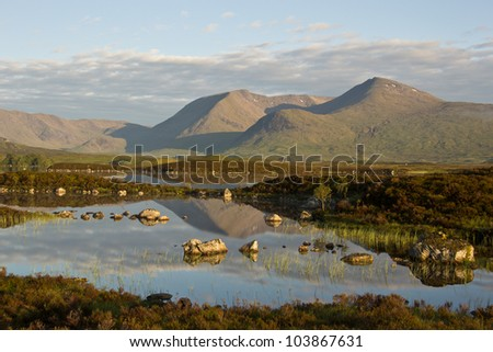 A beautiful sunrise on Rannoch Moor in Scotland with a great view over the so-called Black Mount, reflected in Loch Nah-Achlaise. - stock photo