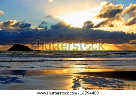 A beautiful sunset at Maori Bay, Muriwai,  on the west coast of Auckland, New Zealand - stock photo
