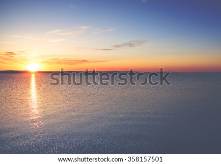 A beautiful sunset from Finland. An image of sun going down behind a big lake. Image has a strong vintage effect applied.  - stock photo