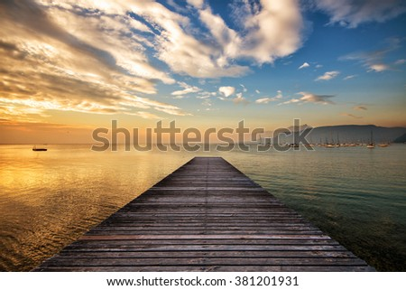a beautiful sunset on the lake in front of the wooden pier - stock photo