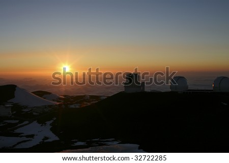 A beautiful sunset on top of Mauna Kea looking at the Observatories on the Big Island of Hawaii - stock photo