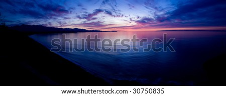 A beautiful sunset over the Strait of Juan de Fuca in Sequim. Panoramic photo. - stock photo