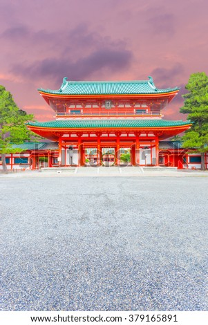 A beautiful sunset sky and centered view of large red front Tower Gate Ro-Mon at the chinowa-kuguri decorated entrance of Heian Jingu Shrine at evening in Kyoto, Japan. Vertical - stock photo