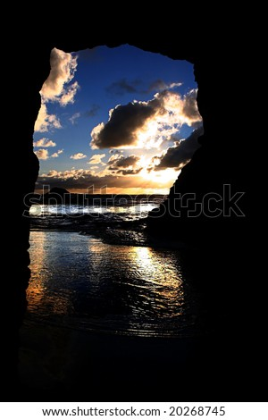 A beautiful sunset taken from within a cave at Maori Bay, Muriwai,on the West Coast of Auckland, New Zealand - stock photo