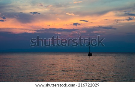 A beautiful sunset view of a fishing boat on calm ocean water with a bright orange blue sky and small waves suggesting calm freedom and peace