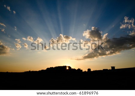 A beautiful sunset with visible rays - stock photo