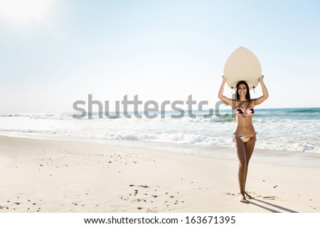 A beautiful surfer girl at the beach holding up her surfboard - stock photo
