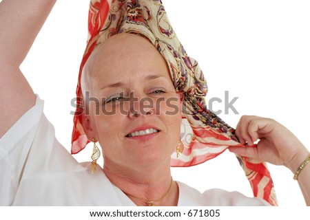 A beautiful survivor removing her scarf to proudly reveal her bald head.  Third in a sequence. - stock photo