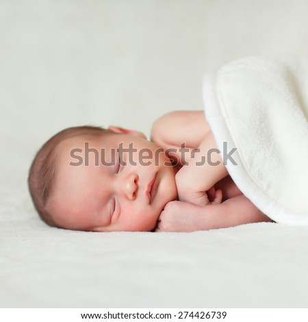 a beautiful sweet newborn baby sleeping on a blanket - stock photo