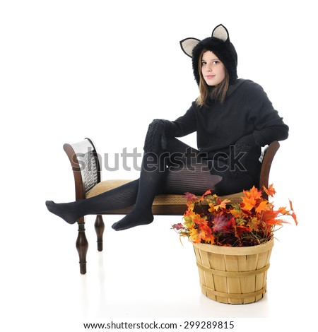 """A beautiful teen black """"cat"""" sitting on a bench with a basket of fall leaves nearby.  On a white background. - stock photo"""