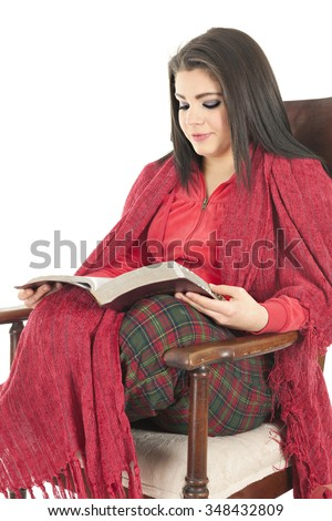 A beautiful teen girl cozied in her Christmas pajamas and a red blanket in a rocking chair reading her Bible.  On a white background. - stock photo