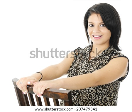 A beautiful teen girl happily holding on as she sits and leans backwards on a wooden chair.  On a white background. - stock photo
