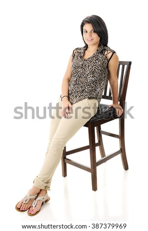 A beautiful teen girl happily leaning on a tall wooden chair.  On a white background.