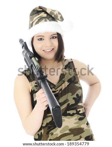 A beautiful teen girl in a sleeveless camouflage shirt and Santa-style camouflage hat.  He happily totes a machine gun over her shoulder.  On white background. - stock photo