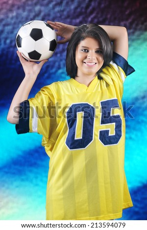 A beautiful teen girl in an over-sized jersey,happily holding a soccer ball behind her head. - stock photo