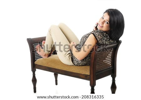 A beautiful teen girl reclined on a bench, happily looking back at the viewer while chatting on her phone.  On a white background. - stock photo
