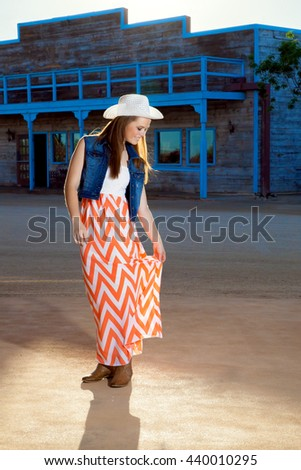 A beautiful, teenage cowgirl looks down with a smile as she adjusts her long skirt.  She is wearing a western hat, denim jacket, long skirt and boots. - stock photo