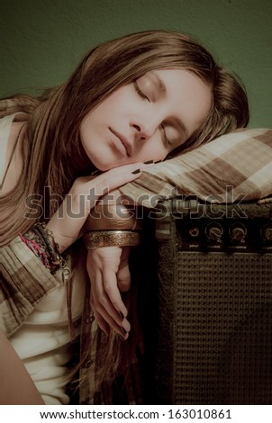A beautiful teenage girl sleeping on a sound amplifier with fashion accessories