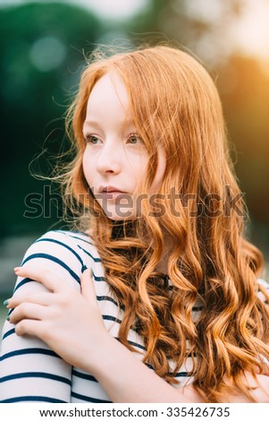 A beautiful teenage girl with long curly ginger hair and green eyes hugging herself in summer park. Outdoor portrait of attractive red-haired young woman in evening at sunset - stock photo