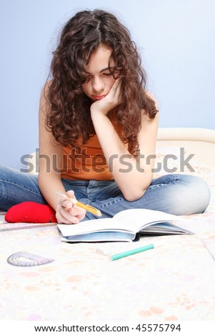 A Beautiful teenager studying on her bed - stock photo