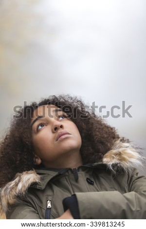 A beautiful thoughtful sad thinking mixed race African American girl or young woman looking up outside on a foggy or misty day - stock photo