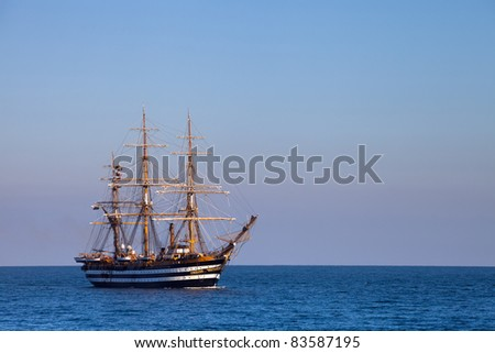 A beautiful three-masted sailboat in the open sea - stock photo