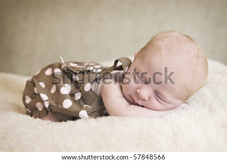 A beautiful three week old baby girl sleeping, soft focus - stock photo