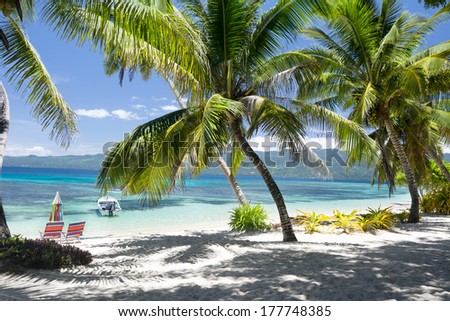 A beautiful tropical beach setting looking out to the turquoise ocean and coral reef.