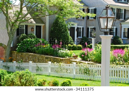 A beautiful vacation home in summer with a vibrant flower garden. - stock photo
