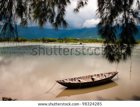 A beautiful vietnamese landscape with a wooden boat - stock photo