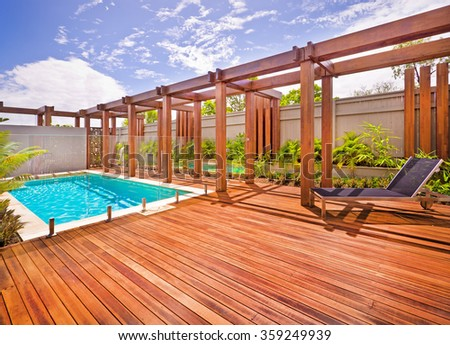 A beautiful view of pool in house in  a sunny day  with wooden floor with a bench - stock photo