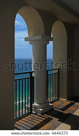 A beautiful view of the ocean and waves through the arches of a balcony. - stock photo