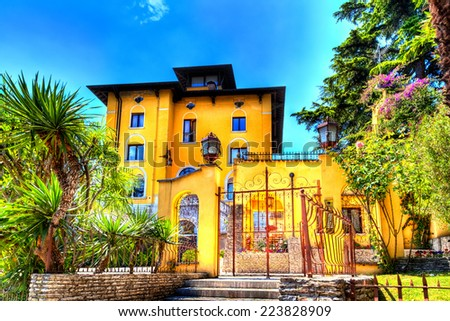 A beautiful villa in Sirmione at the Lake Garda with exotically garden lights up in yellow colorshades like painted - stock photo