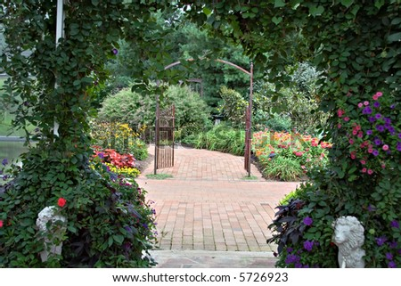 A Beautiful Vine Covered Arbor Frames The Path And Distant Garden Gate.