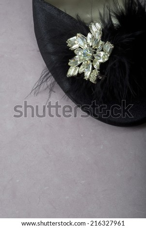 A beautiful vintage rhinestone broach on a black woman's slipper with feather on the toe. - stock photo