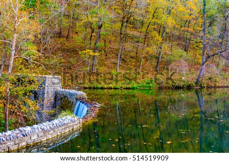 A beautiful waterfall can be seen in this autumn image at Mirror Lake, Arkansas with fall colors such as red, green, gold, yellow and green.