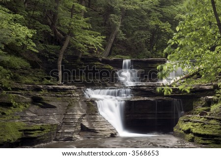A beautiful waterfall in one of New York's many gorges in the finger lakes region. Green colors of spring  along the stream add to the beauty of the scene. - stock photo