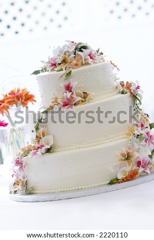 a beautiful wedding cake with a georgeous candy flower arrangement. This image is heavily back lit with a blown out background - stock photo