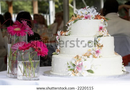 a beautiful wedding cake with a gorgeous candy flower arrangement. This cake is sitting on a table with two vases with flowers, people are sitting in the background - stock photo