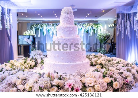 A beautiful wedding cake with decoration at wedding reception room for wedding party. Beautiful Cakes dessert and flower decorate in event party room. White Cake Design in Wedding Room with blue light - stock photo